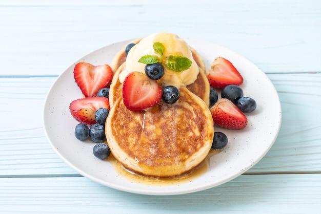Pancake with blueberries, strawberries, honey and vanilla ice cream