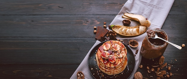 검은 접시에 초콜릿과 견과류 페이스트, 호두, 바나나를 넣은 팬케이크