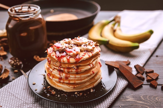 Pancake with chocolate and nut paste, walnuts and banana on a black plate