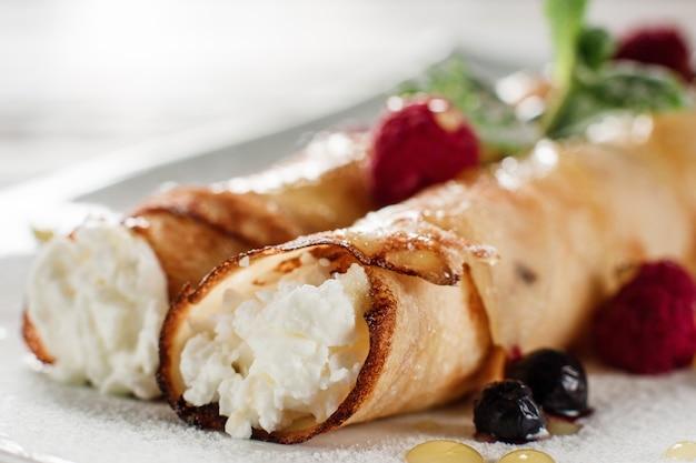코티지 치즈 팬케이크를 닫습니다. 하얀 접시에 라스베리와 수 제 압 연된 디저트입니다.