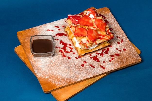 木の板にイチゴとクリームのパンケーキ