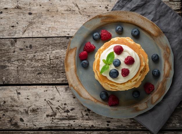 バニラクリーム、ブルーベリー、ラズベリーのパンケーキ。上面図、スペースをコピーします。素朴な