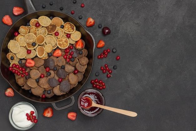 Блины и ягоды на сковороде. йогурт и варенье на столе. черная поверхность. плоская планировка. копировать пространство