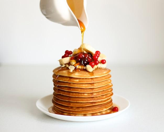 パンケーキはベリーとバナナで飾られ、メープルシロップまたは蜂蜜が注がれています。