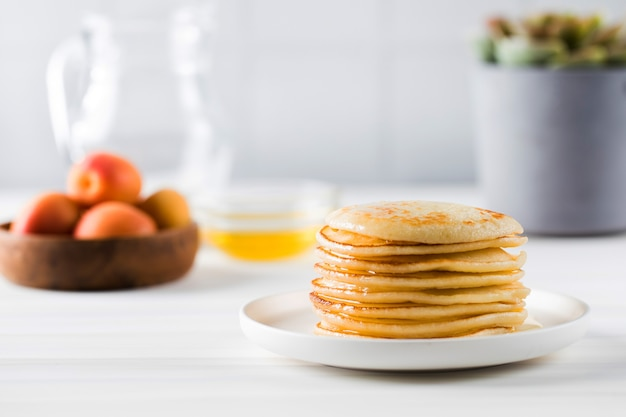 The pancakes are stacked in a plate in the background a bowl of honey fruit and a jug of milk