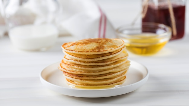 The pancakes are stacked in a plate in the background a bowl of honey and a jug of milk