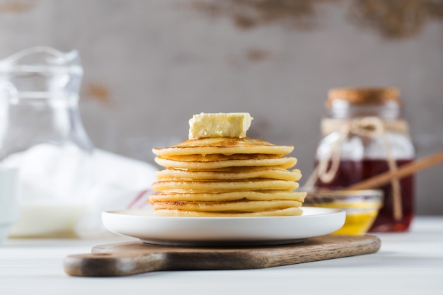 The pancakes are stacked in a plate with a piece of butter and drizzled with honey sauce breakfast c...