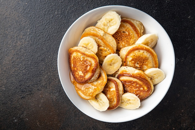 パンケーキバナナスライスシロップまたは蜂蜜おいしい朝食甘いデザート新鮮な部分を食べる準備ができて