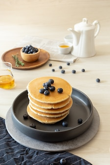 Pancakes and blueberries served with hot tea