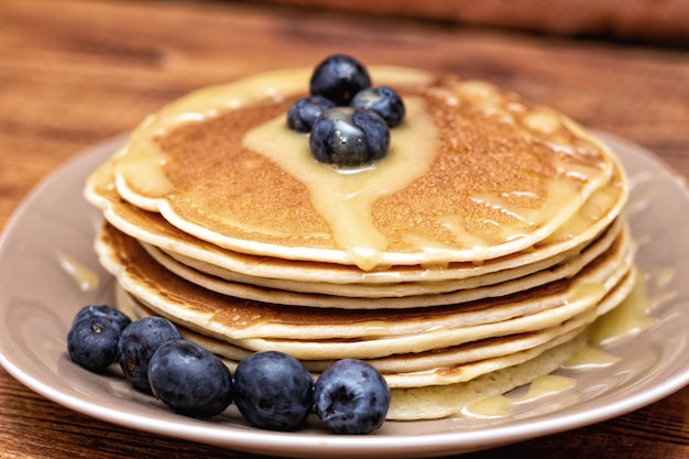 Pancakes on the brown wooden background