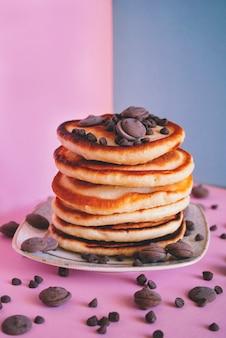 팬케이크는 분홍색 표면에 둥근 초콜릿 조각으로 닫힙니다.