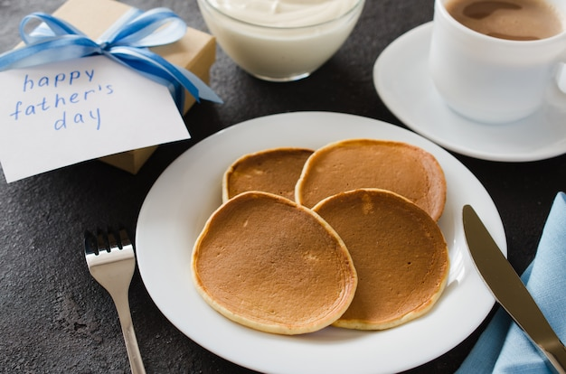 Pancakes and a cup of coffee for father. father's day concept.