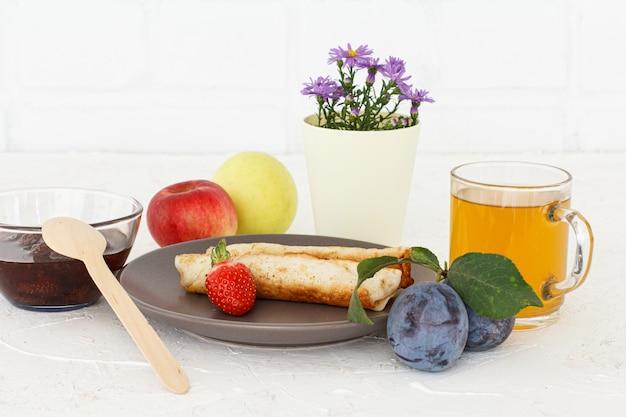 흰색 벽돌 배경에 치즈, 그릇에 잼, 차 한잔, 식물 등으로 가득 찬 팬케이크
