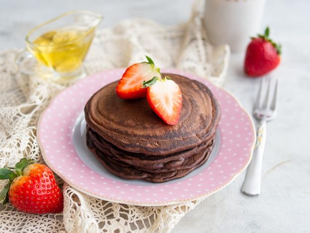 딸기와 꿀을 곁들인 새 체리 가루로 만든 팬케이크. 건강한 아침 식사. 확대.