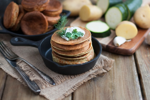 Pancakes from vegetables in a cast-iron frying pan on a wooden background