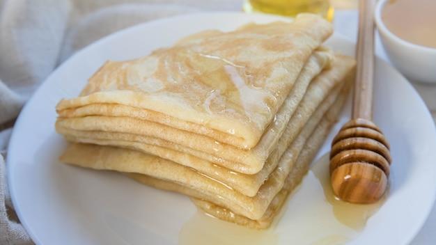 白いプレートに蜂蜜と木製の蜂蜜スプーンをパンケーキ