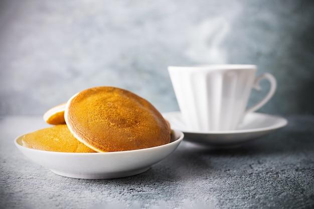 접시에 팬케이크와 회색 표면에 증기와 도자기가 있는 흐릿한 차 또는 커피