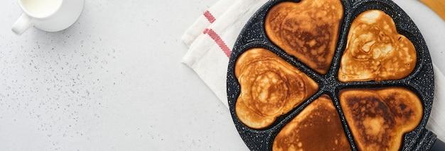 회색 세라믹 접시에 초콜릿 소스를 넣은 아침 식사 하트 모양의 팬케이크, 회색 콘크리트 배경에 커피 한 잔. 발렌타인 데이 아침 식사를 위한 테이블 설정입니다. 상위 뷰 복사 공간입니다. 배너.