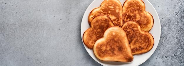 회색 콘크리트 배경에 있는 회색 세라믹 접시에 초콜릿 소스를 넣은 아침 식사 하트 모양의 팬케이크. 좋아하는 발렌타인 데이 아침 식사를 위한 테이블 설정 상위 뷰 복사 공간