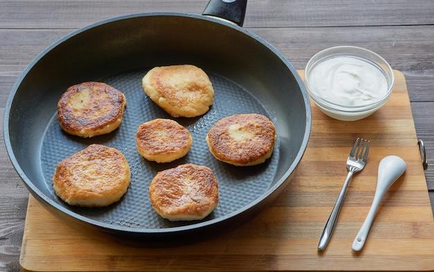 사워 크림과 함께 작은 접시와 프라이팬에 두부 치즈로 만든 팬케이크