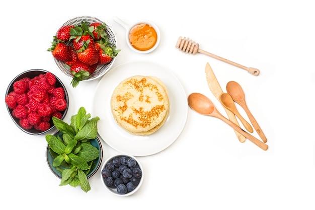 皿の上のパンケーキと白い背景と上面図のボウルのベリー