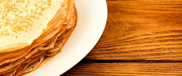 木製のテーブルの上の皿の上のパンケーキ新鮮なパンケーキの大きなスタックおいしい新鮮なパンケーキ