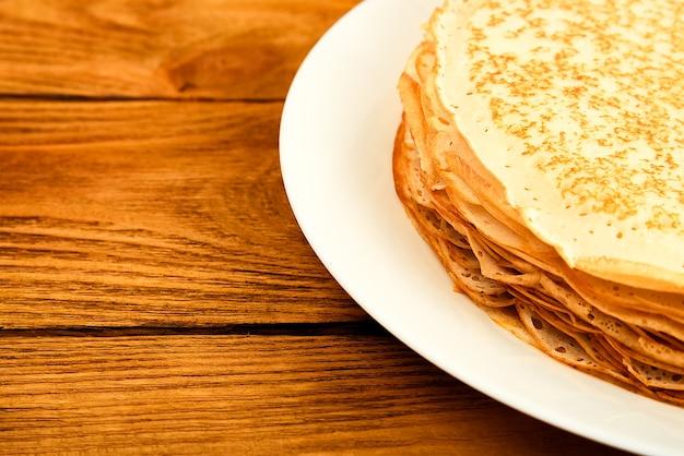 Блины на тарелке на деревянном столе. большая стопка свежих блинов. вкусные здоровые свежие блины. место для рекламы, логотипа, надписи, макета, макета.