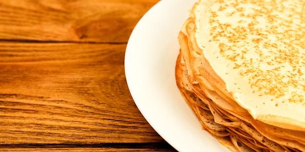 Блины на тарелке на деревянном столе большая стопка свежих блинов