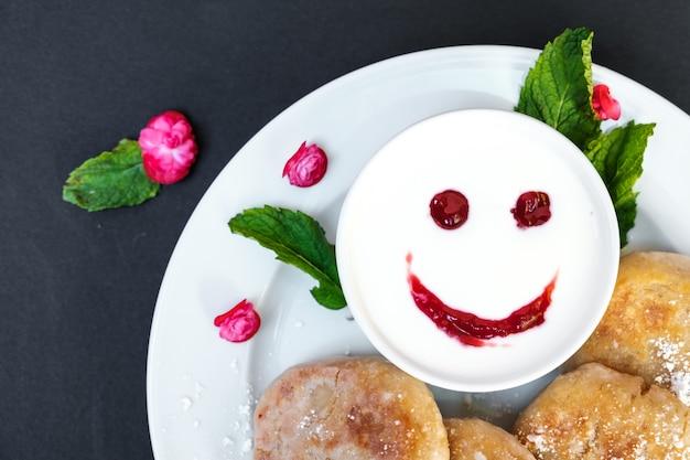 黒の背景にサワークリームとプレート上のパンケーキ。笑顔で陽気な朝食クローズアップ