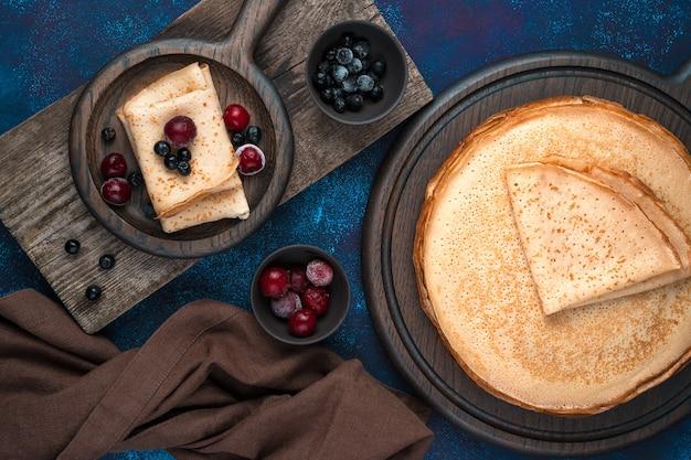 보드와 서빙 접시에있는 팬케이크에는 체리와 마가목이 뿌려집니다.