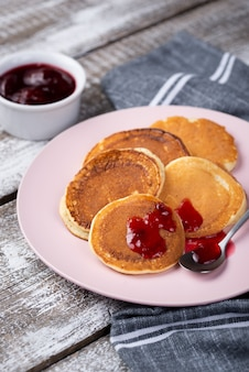 Pancakes on plate for breakfast with jam and spoon