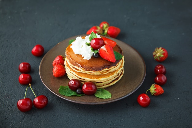 Pancakes in a plate with strawberries, whipped cream, mint, honey and cherry on a dark black background