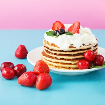 Pancakes in a plate with whipped cream, honey, strawberries, mint and sweet cherries on a bright blue and pink background.
