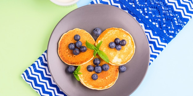 Pancakes served with blueberries on gray plate