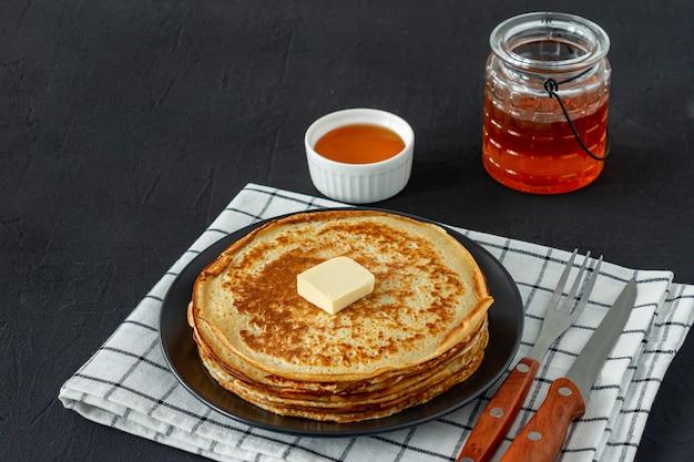 팬케이크는 어두운 접시에 꿀 시럽과 버터와 함께 제공됩니다. 팬케이크 주간 또는 shrovetide를 위한 전통 크레이프.