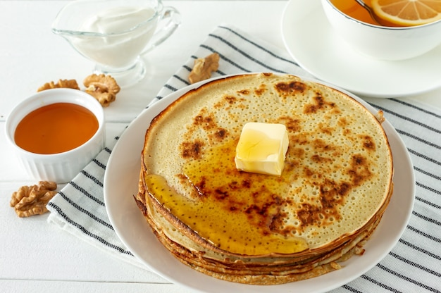 白い皿にハニーシロップとバターを添えたパンケーキ。パンケーキウィークまたはshrovetideの伝統的なクレープ。