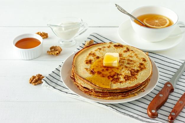 팬케이크는 하얀 접시에 꿀 시럽과 버터와 함께 제공됩니다. 팬케이크 주간 또는 shrovetide를 위한 전통 크레이프.