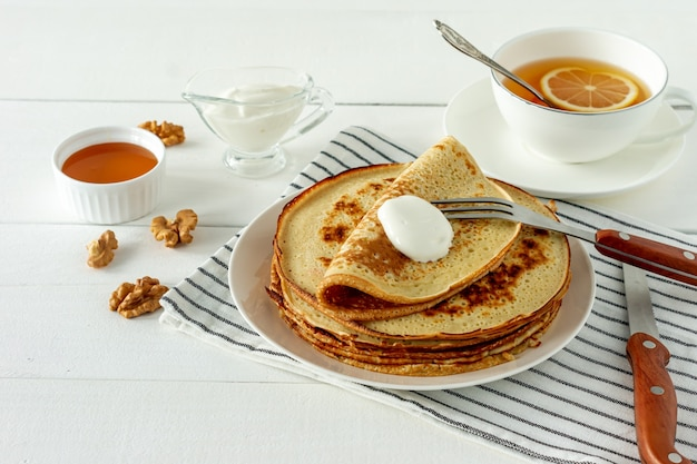팬케이크는 하얀 접시에 꿀 시럽과 사워 크림과 함께 제공됩니다. 팬케이크 주간 또는 shrovetide를 위한 전통 크레이프.