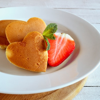 Pancakes in the shape of a heart with berries.