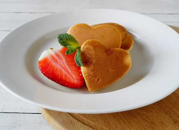 Pancakes in the shape of a heart with strawberries.