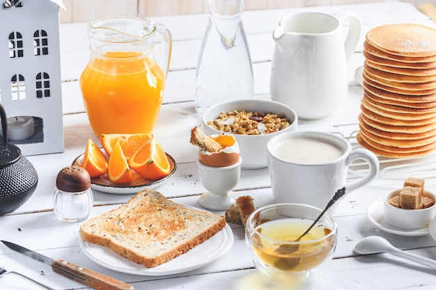 Pancakes, soft-boiled egg, toast, oatmeal, granola, fruit, coffee, tea, orange juice, milk on white wood