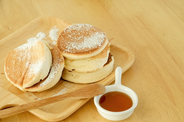 팬케이크, 나무 쟁반에 착빙 설탕을 뿌린다. 나무 테이블에 놓인 컵에 꿀과 함께 제공됩니다.