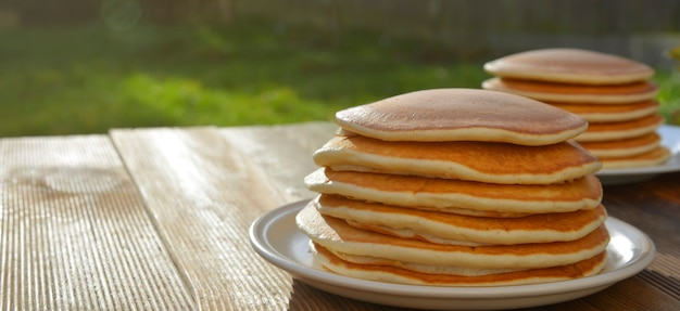 Pancakes. stack of isolated american pancakes over wooden table. breakfast, food.