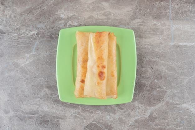 Блины сложены на зеленом блюде на мраморной поверхности