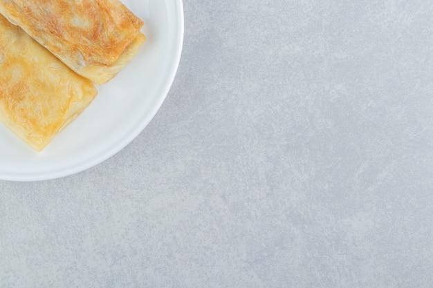 Блины с начинкой из мяса на белой тарелке.