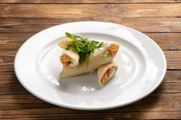 나무 식탁에 흰색 세라믹 접시에 연어, 크림 치즈, 양상추 및 arugula로 채워진 팬케이크