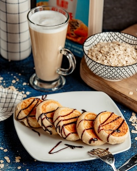 Pancakes topped with chocolate syrup and cappuccino