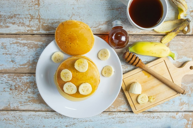 Pancakes topped with honey and bananas on the table