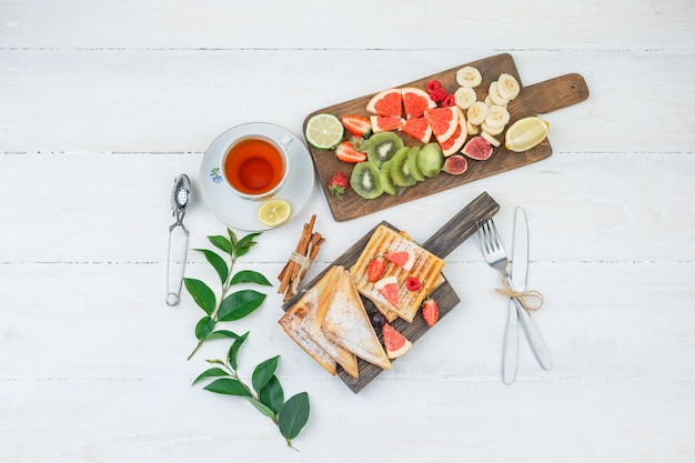 Pancakes and waffles on wooden board with tea and fruit
