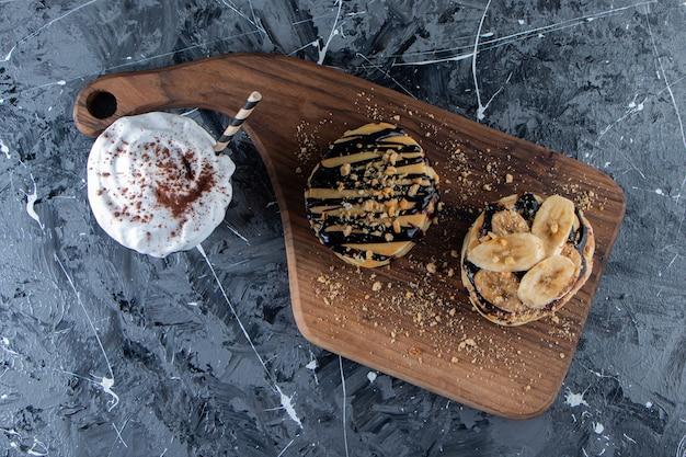맛있는 커피와 함께 나무 판자에 바나나와 초콜릿 토핑을 얹은 팬케이크.